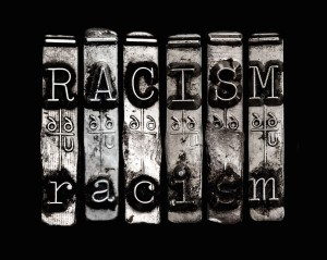 "Silver typewriter typebars are arranged against a black background. They spell ""racism"" in all capital and lowercase letters. Photo by bradcalkins."
