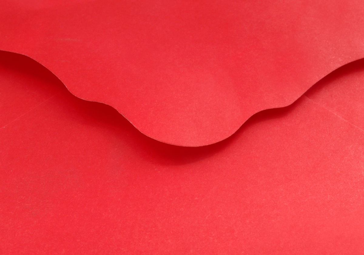 Close-up of a vibrant red envelope, its ornate flap slightly raised, photo by Victor Burnside