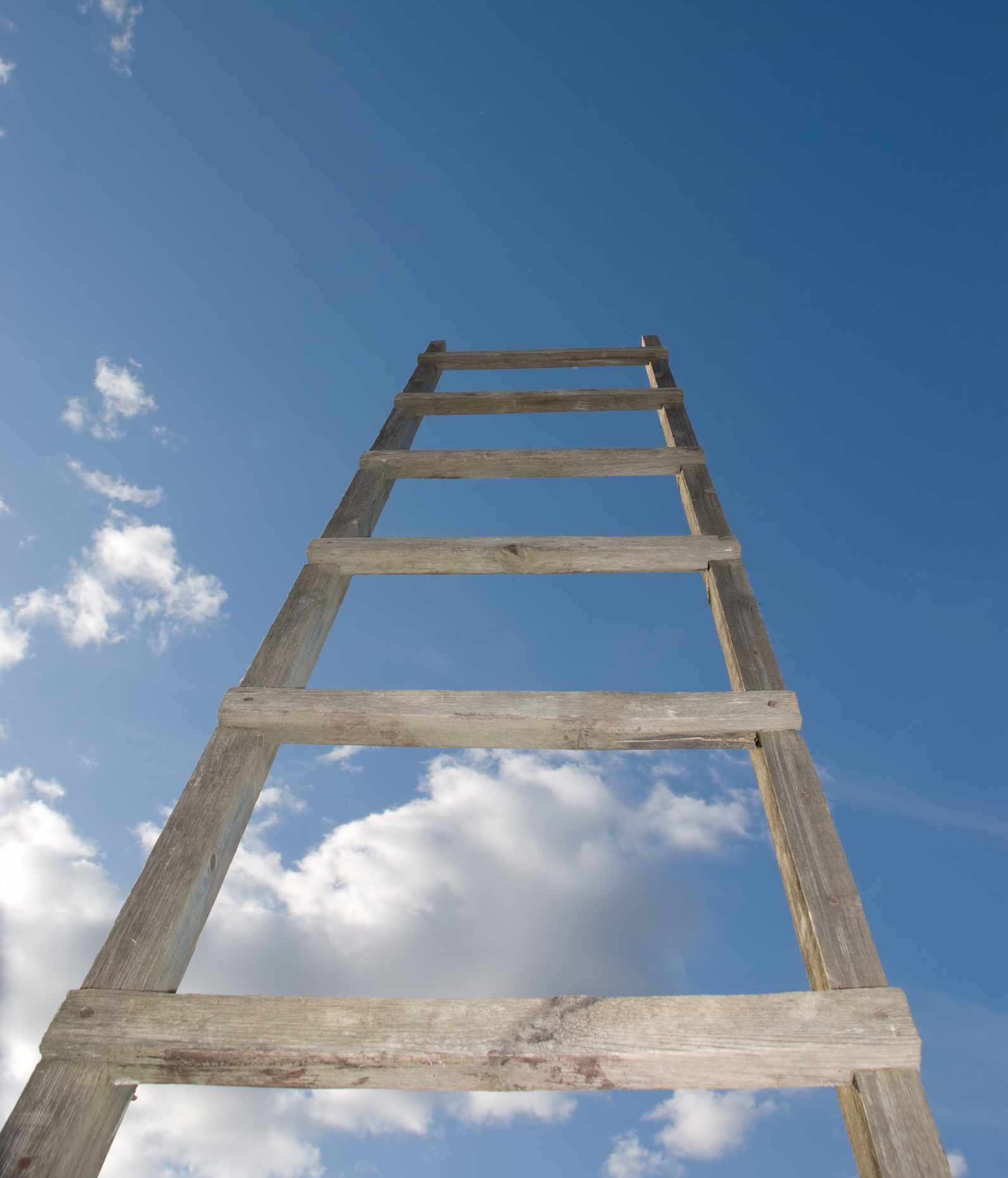 A weathered wooden ladder extending into the sky, but connecting to nothing, photo by Yury Shirokov