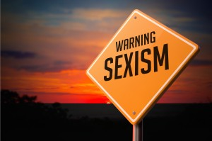 "Yellow road sign set against a vibrant sunset reads, ""Warning Sexism"". Photo by tashatuvango."