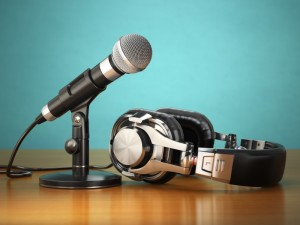 A stand-mounted microphone sits in front of a pair of headphones against a teal background. Photo by Maksym Yemelyanov.