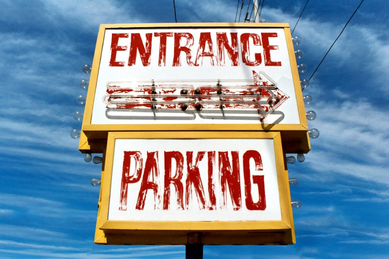 """Large weathered sign reads """"entrance"""" in fading red letters, underneath an unlit neon arrow points the way, photo by Sarah Post"""