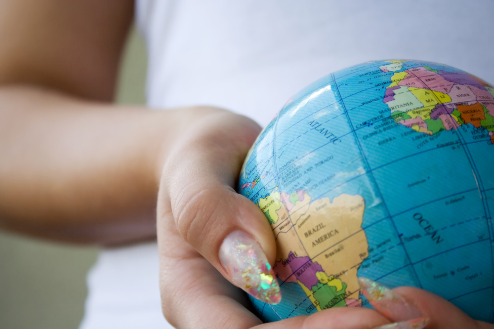 Brown hands with sparkling nails gently holding a small globe, photo by Qtrix