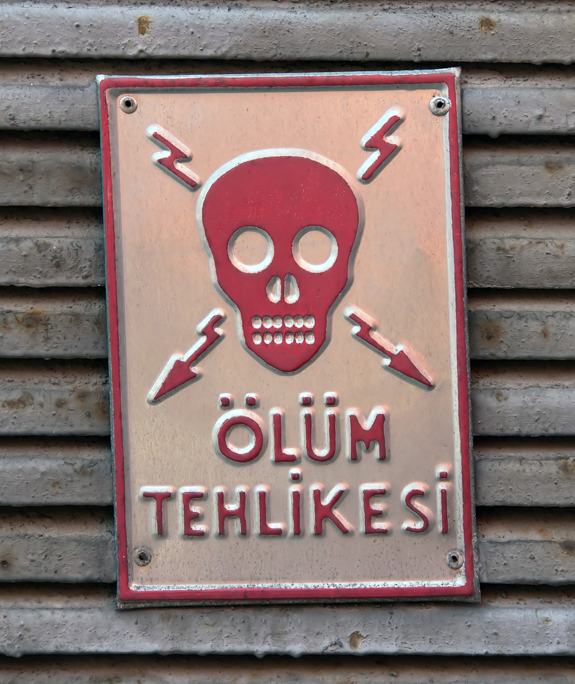 Stern metal sign featuring a skull and crossbones composed of electricity, German wording underneath, photo by Tuncay Demir